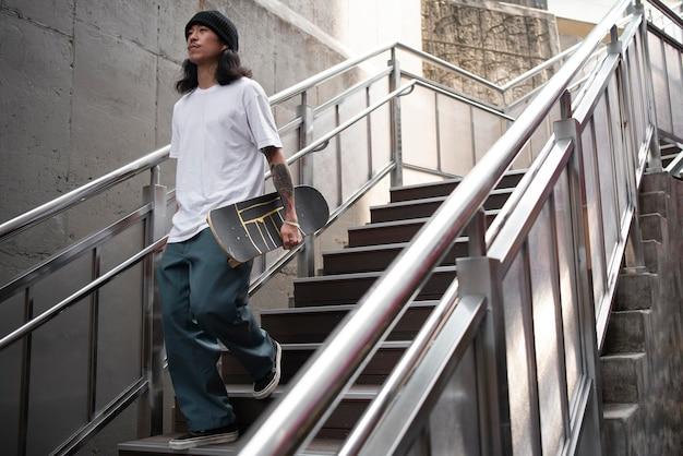 Jeune homme asiatique tenant sa planche à roulettes