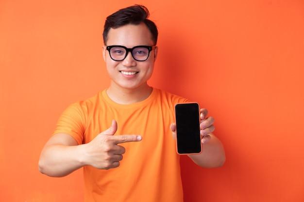 Jeune homme asiatique tenant le téléphone avec une expression excitée