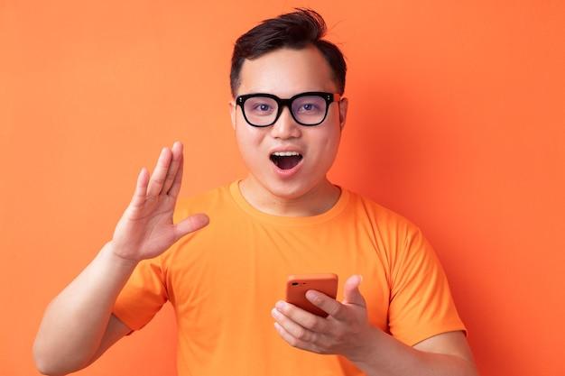 Jeune homme asiatique tenant le téléphone avec une expression de surprise