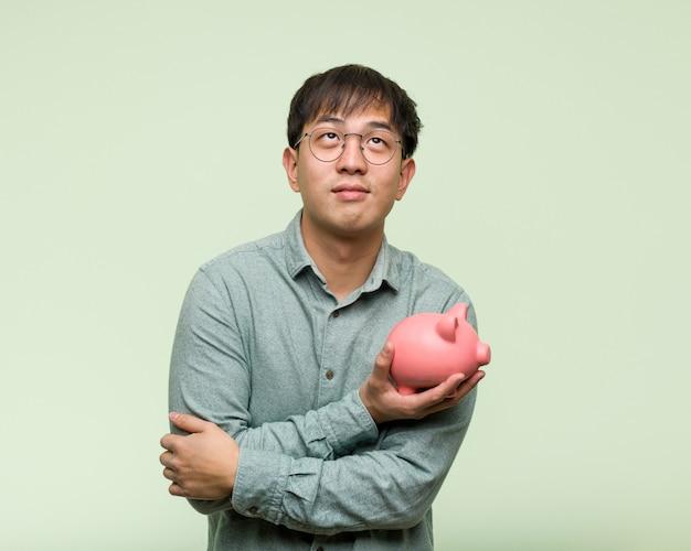 Jeune homme asiatique tenant une tirelire souriant confiant et croisant les bras, levant