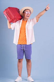 Jeune homme asiatique tenant une valise rouge sur fond bleu