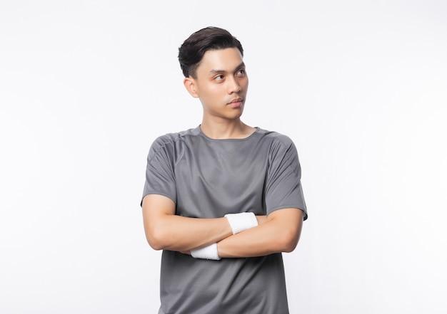 Jeune homme asiatique en tenue de sport bras croisés et à la recherche de fond isolé