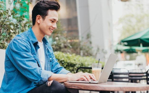 Jeune homme asiatique travaillant au café