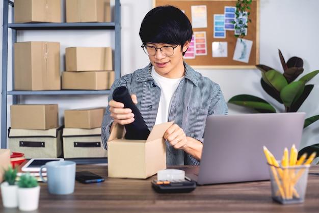 Jeune homme asiatique travaillant sur le bureau de service de livraison