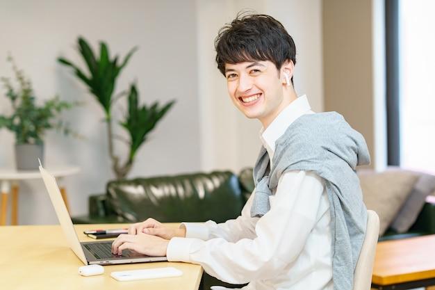 Jeune homme asiatique utilisant un ordinateur portable dans une pièce décontractée