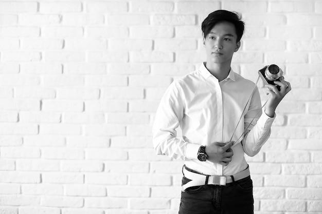 Un jeune homme asiatique utilise un appareil photo en studio