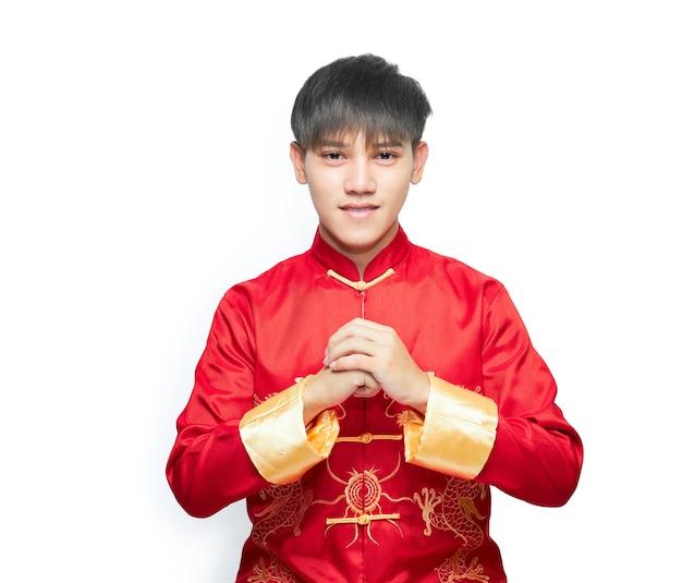 Jeune homme asiatique vêtu d'une robe rouge à col mandarin montrant un geste de félicitations au festival de joyeux nouvel an chinois.