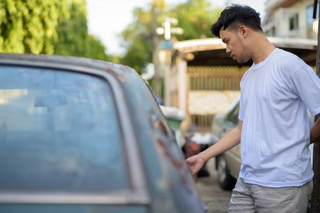 Jeune homme asiatique avec vieille voiture rouillée dans les rues à l'extérieur