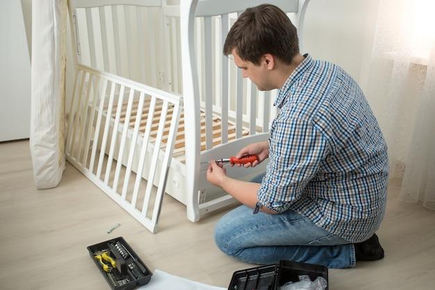 Jeune homme assemblant le lit de bébé après avoir emménagé dans une nouvelle maison