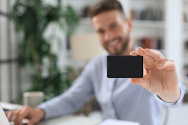 Jeune homme assis au bureau et paie par carte de crédit avec sa tablette.