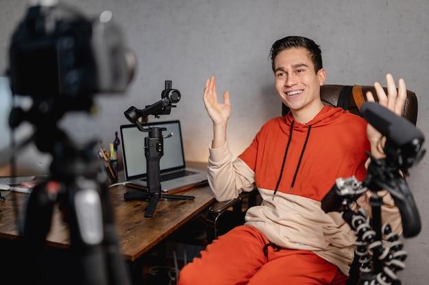 Jeune homme assis au bureau parlant à la caméra. guy enregistre une vidéo avec des équipements professionnels. vlog, concept indépendant.