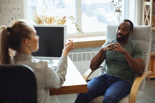Jeune homme assis au bureau pendant l'entretien d'embauche avec une employée, une patronne ou une responsable des ressources humaines, parlant, pensant, a l'air confiant. concept de travail, travail, affaires, finances, communication.
