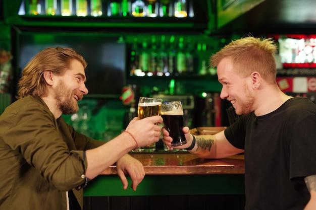 Jeune homme assis au comptoir du bar et buvant de la bière avec son ami