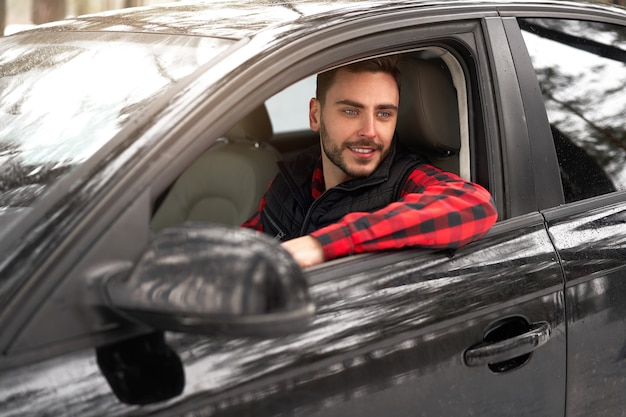 Jeune homme assis au volant de sa voiture