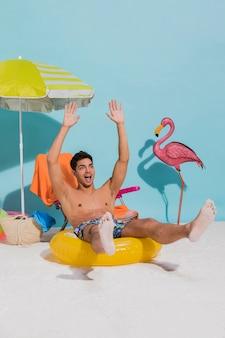 Jeune homme assis sur une bouée de sauvetage levant les mains en l'air