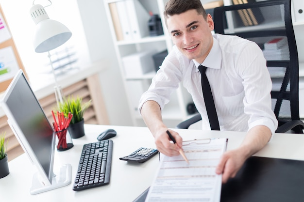 Un jeune homme assis à un bureau d'ordinateur dans le bureau et travaillant avec des documents.