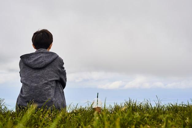 Jeune homme assis et buvant du café pour regarder la brume matinale.