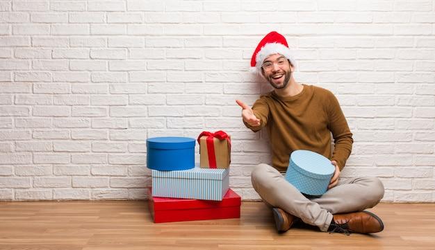 Jeune homme assis avec des cadeaux pour célébrer noël tendre la main pour saluer quelqu'un
