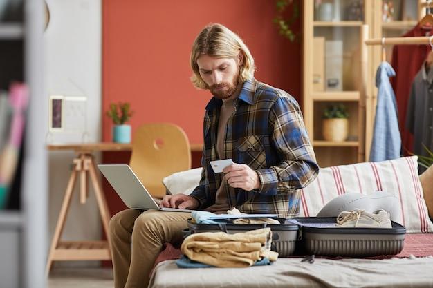 Jeune homme assis sur un canapé avec ordinateur portable et payer les billets en ligne avant son voyage