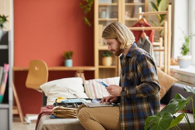 Jeune homme assis sur un canapé avec un ordinateur portable sur ses genoux et commander des billets d'avion en ligne