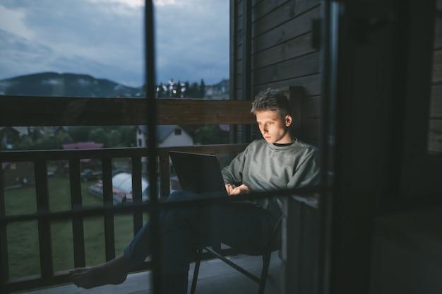 Jeune homme assis sur une chaise sur un balcon à l'aide d'un ordinateur portable