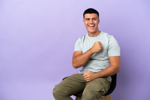 Jeune homme assis sur une chaise sur fond isolé célébrant une victoire