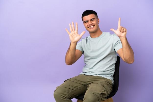 Jeune homme assis sur une chaise sur fond isolé comptant sept avec les doigts