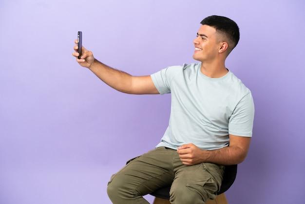 Jeune homme assis sur une chaise sur fond isolé faisant un selfie