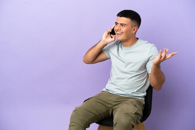 Jeune homme assis sur une chaise sur fond isolé en gardant une conversation avec le téléphone portable avec quelqu'un