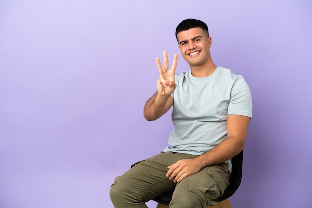 Jeune homme assis sur une chaise sur fond isolé heureux et comptant trois avec les doigts