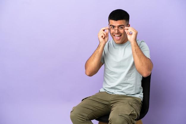 Jeune homme assis sur une chaise sur fond isolé avec des lunettes et surpris