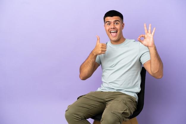 Jeune homme assis sur une chaise sur fond isolé montrant un signe ok et un geste du pouce vers le haut