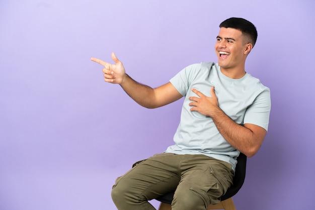 Jeune homme assis sur une chaise sur fond isolé, pointant le doigt sur le côté et présentant un produit