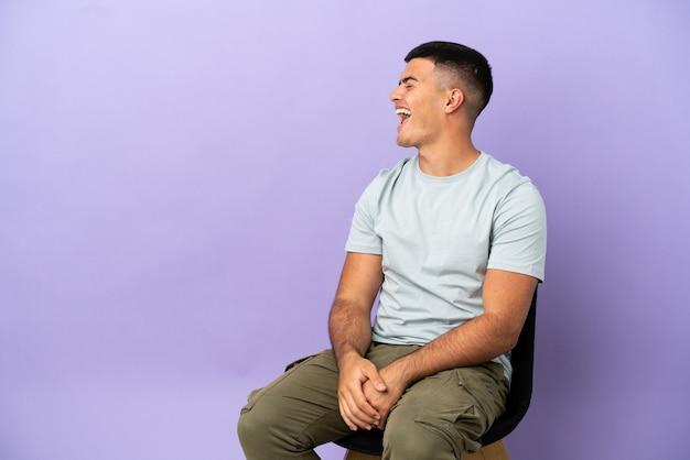 Jeune homme assis sur une chaise sur fond isolé en riant en position latérale