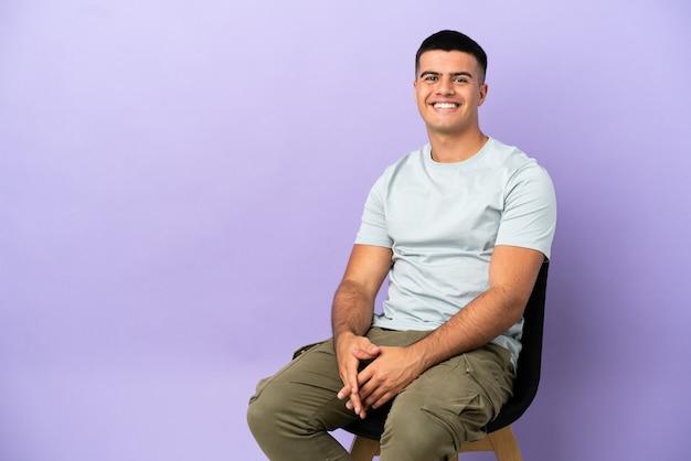 Jeune homme assis sur une chaise sur fond isolé en riant