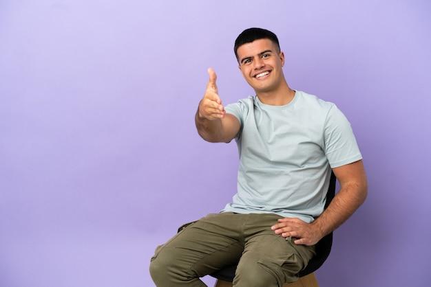 Jeune homme assis sur une chaise sur fond isolé se serrant la main pour conclure une bonne affaire