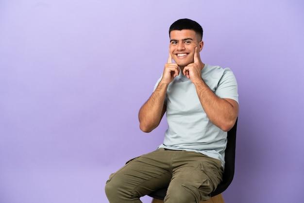Jeune homme assis sur une chaise sur fond isolé souriant avec une expression heureuse et agréable