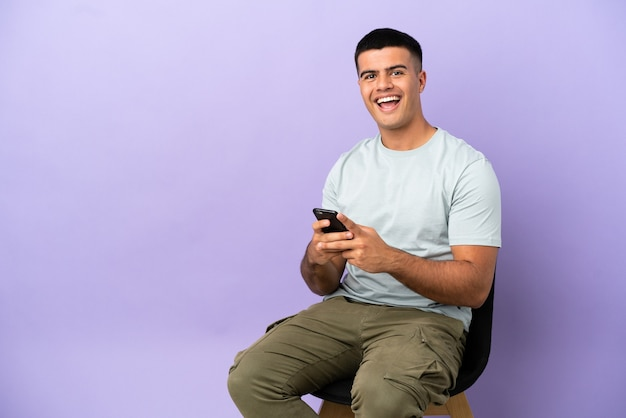 Jeune homme assis sur une chaise sur fond isolé surpris et envoyant un message