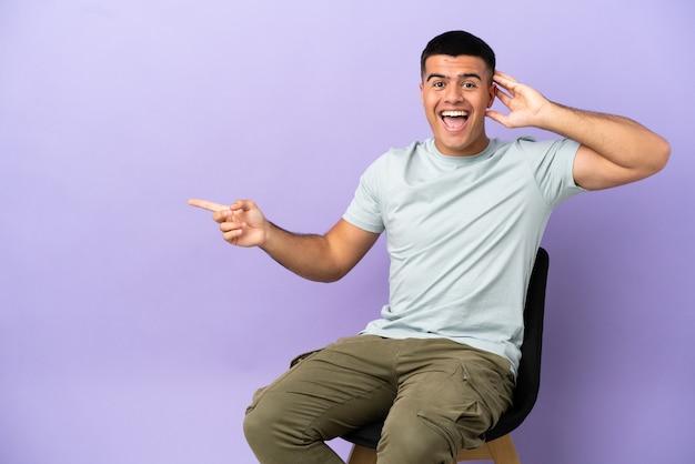 Jeune homme assis sur une chaise sur fond isolé surpris et pointant le doigt sur le côté