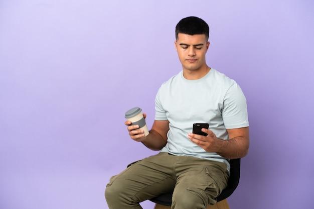 Jeune homme assis sur une chaise sur fond isolé tenant du café à emporter et un mobile