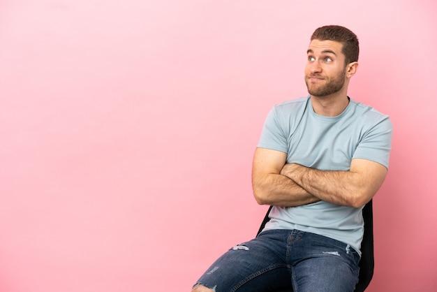 Jeune homme assis sur une chaise sur fond rose isolé faisant un geste de doute tout en soulevant les épaules