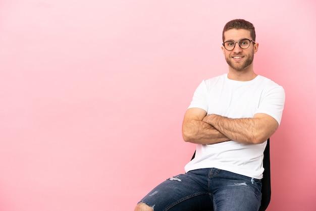 Jeune homme assis sur une chaise sur fond rose isolé en gardant les bras croisés en position frontale