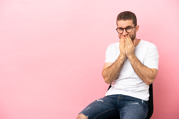 Jeune homme assis sur une chaise sur fond rose isolé heureux et souriant couvrant la bouche avec les mains