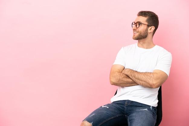 Jeune homme assis sur une chaise sur fond rose isolé heureux et souriant