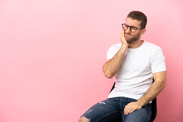 Jeune homme assis sur une chaise sur fond rose isolé avec mal de dents