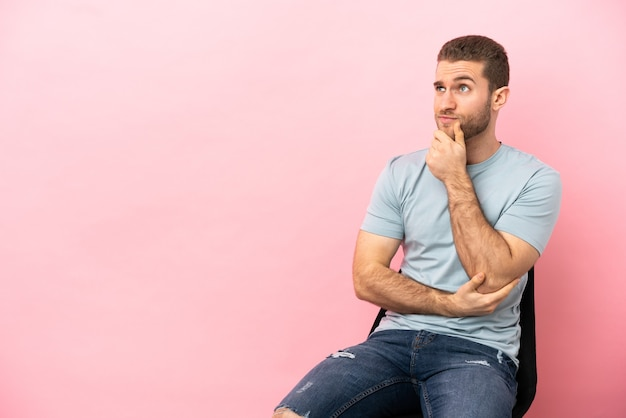 Jeune homme assis sur une chaise sur fond rose isolé pensant à une idée tout en levant les yeux