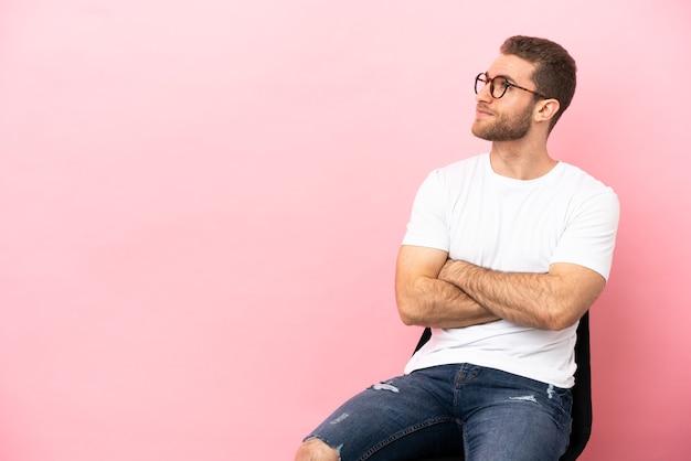 Jeune homme assis sur une chaise sur fond rose isolé regardant sur le côté