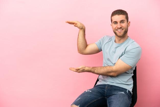 Jeune homme assis sur une chaise isolée tenant un espace pour insérer une annonce