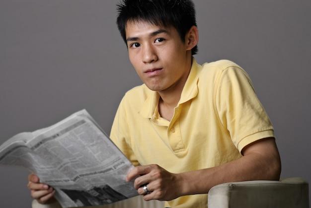 Jeune homme assis sur une chaise et lire le journal