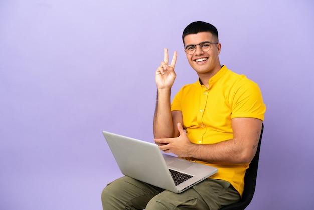 Jeune homme assis sur une chaise avec un ordinateur portable souriant et montrant le signe de la victoire